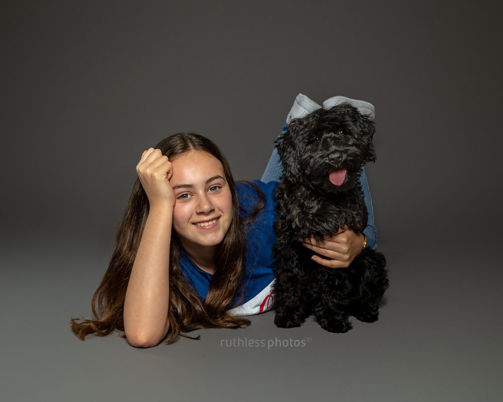 black tamaruke labradoodle puppy with female owner on grey background